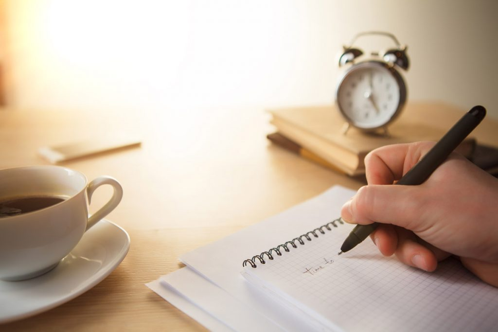 The male hand with a pen and the service hours and notebook on the table.