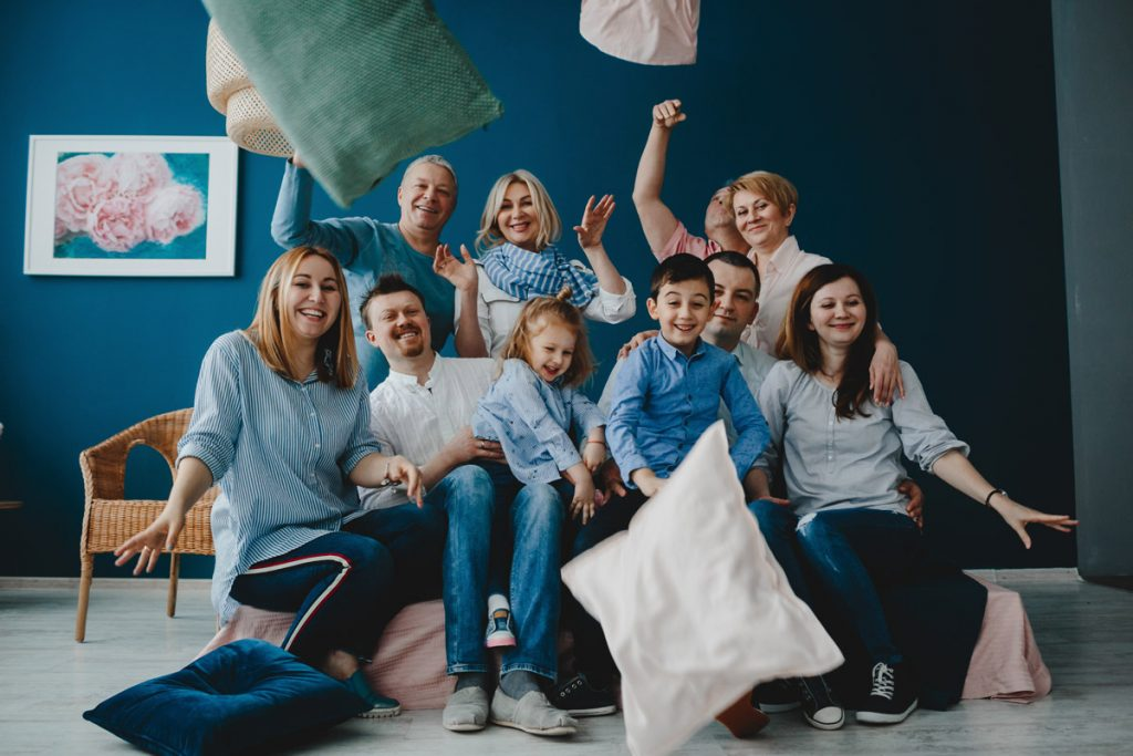 Grandparents, parents and their little children sit together on the bed in a blue room and fight pillows.