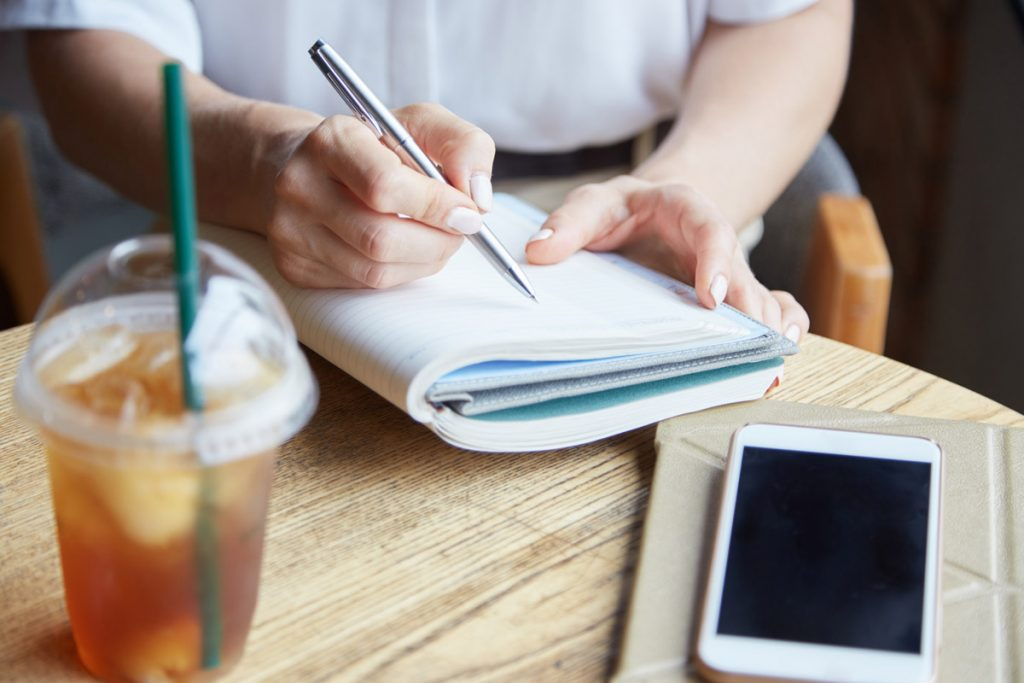 Hands of female student sitting at cafe table and writing essay in textbook.
