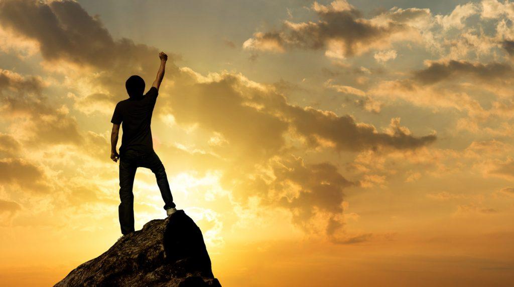 Man on the peak of mountain and sunlight , success,winner concept.