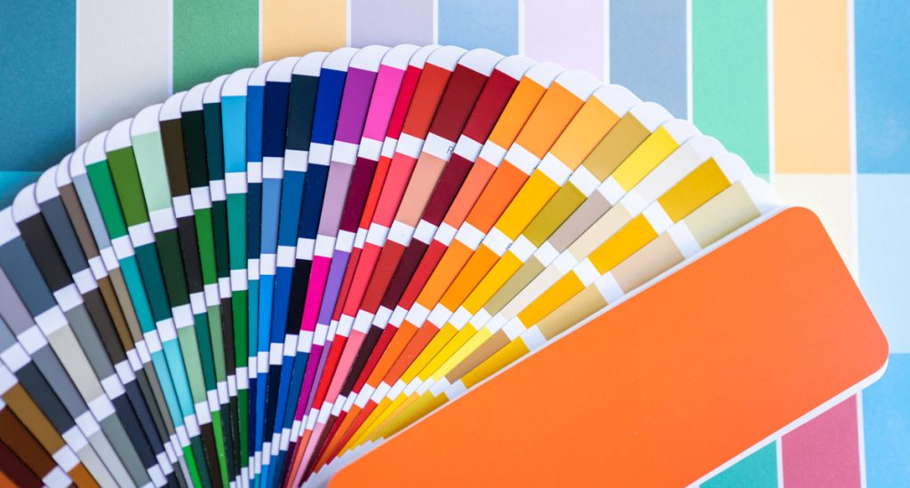 Color swatches of graphic designers putting on desk table in working room.