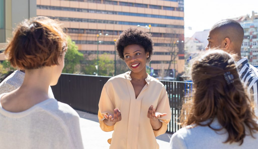 Group of young people standing on street and communicating. Smiling African American woman talking to friends.