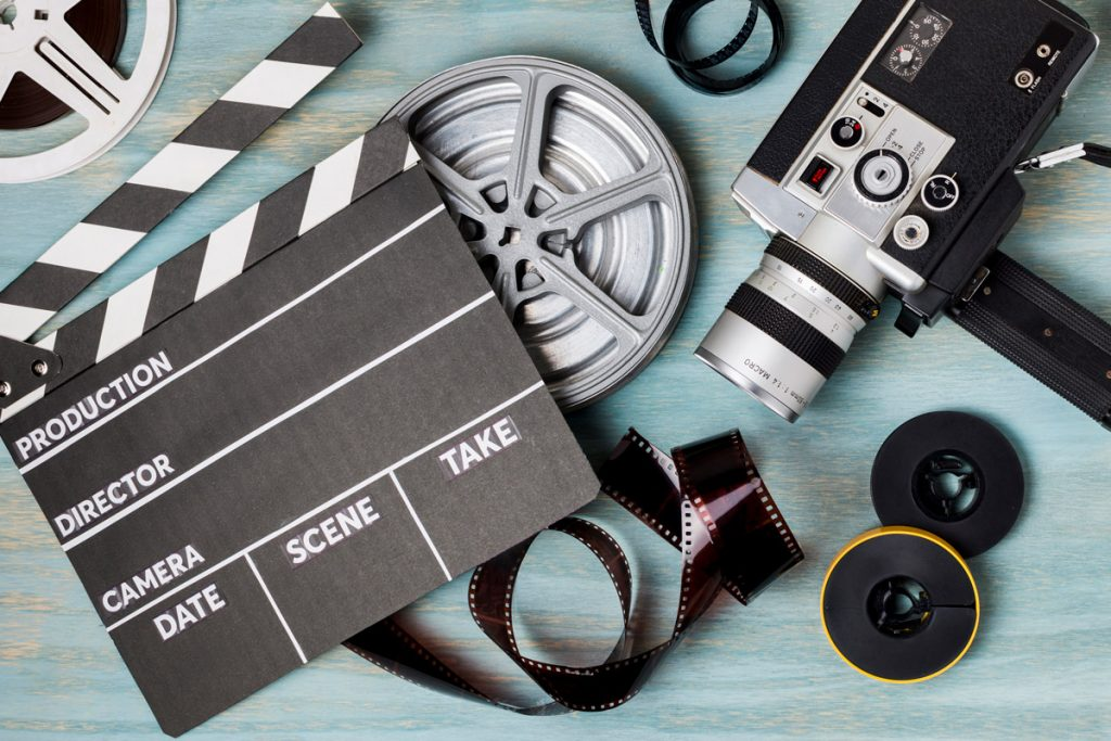 An elevated view of clapperboard; film reels; film strips and camcorder on blue wooden backdrop.