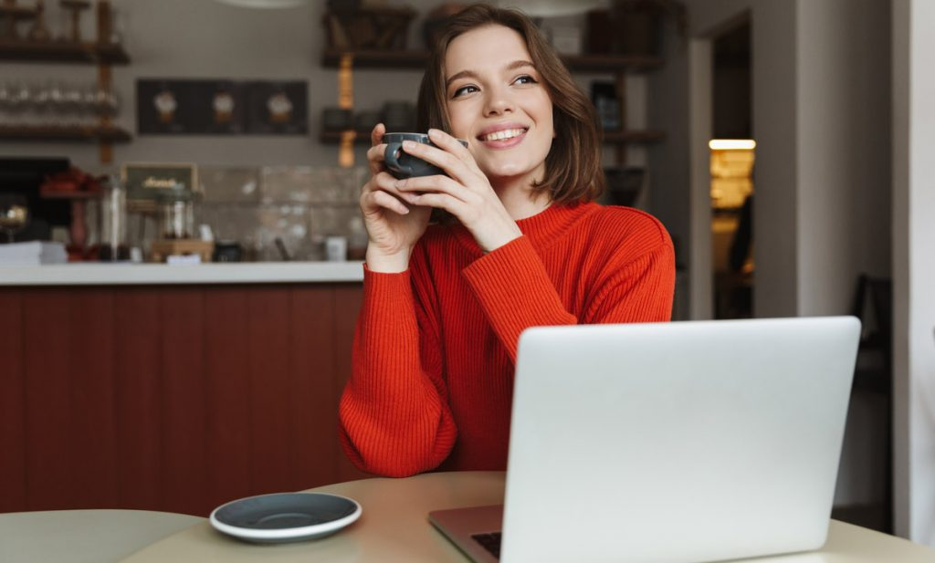 Image of happy caucasian woman 20s smiling while using laptop and drinking coffee in cafe.