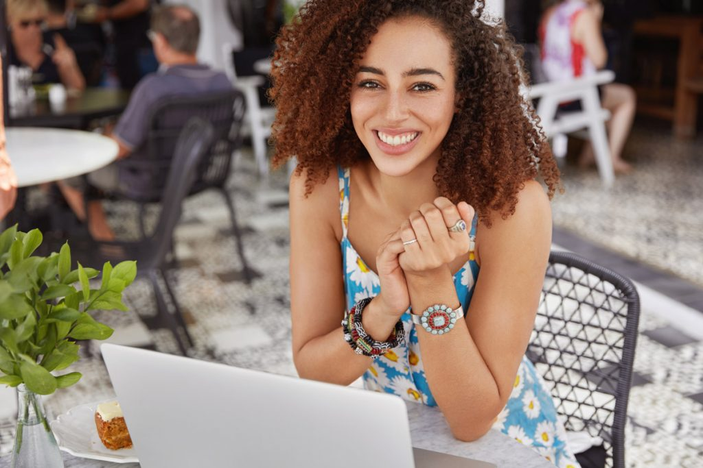 Image of happy dark skinned young female with Afro hair style, has positie expression, sits in modern coffee shop, connected to wireless internet and works on laptop computer, does distance work.