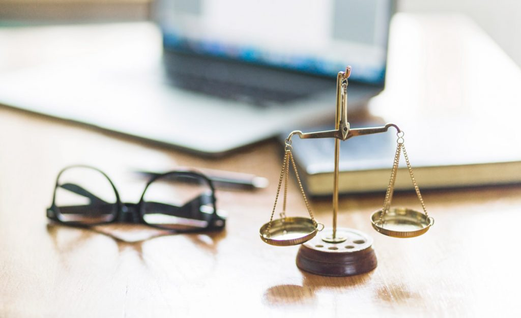 Justice scale and spectacles on wooden desk in courtroom.